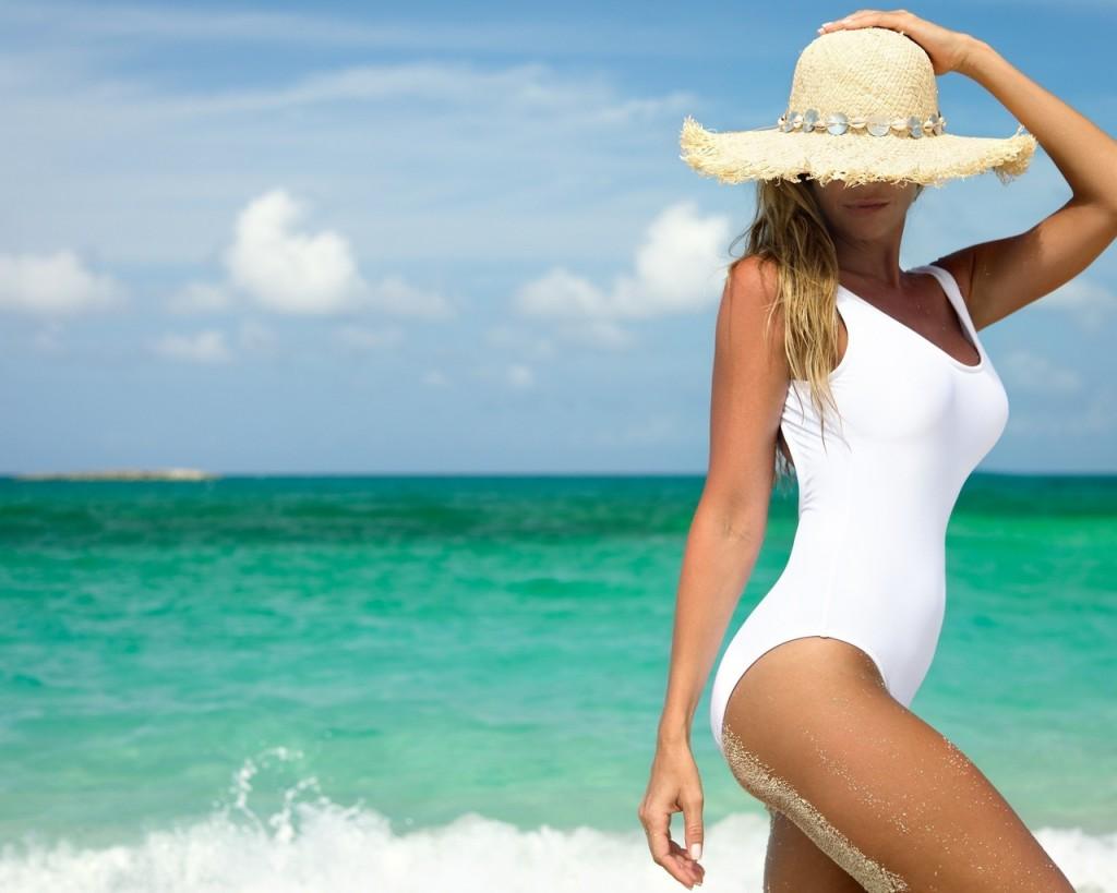 Девушка в купальнике идет по пляжу